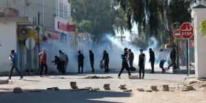 "Tunisian protesters take to the streets in the southern town of Kasserine , Tunisia, and clash with riot police during a protest against a new tax on vehicles, Wednesday, Jan. 8, 2014. Protesters called the government the ""assassin of our dreams,"" complaining that little has changed since the country's reviled leader was ousted in 2011. (AP Photo / Mouldi Kraiem)"